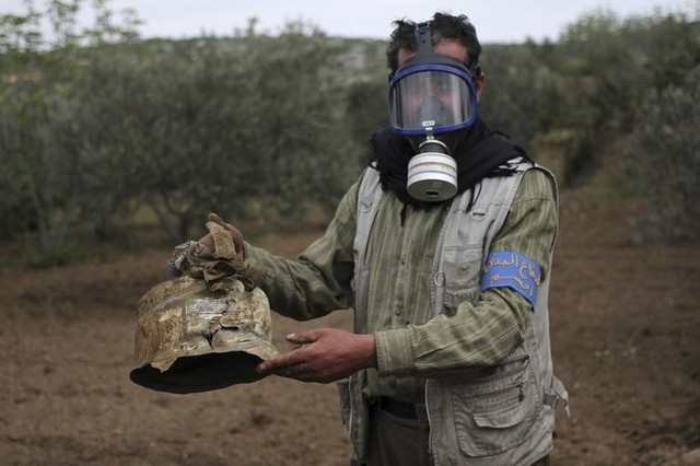 A Civil Defence member carries a damaged canister in Ibleen village from what activists said was a chlorine gas attack, on Kansafra, Ibleen and Josef villages, Idlib countryside, Syria May 3, 2015. Credit: Reuters/Abed Kontar/Files