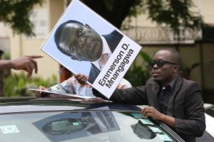 A protester holds a poster showing support for ousted Zimbabwean vice-President Emmerson Mnangagwa, in Harare, Zimbabwe, November 18, 2017. Credit: Reuters/Philimon Bulawayo