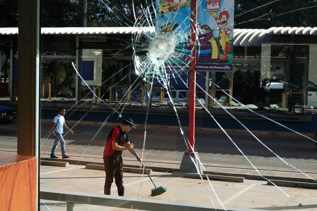 A broken restaurant window is seen after being looted while an employee sweeps the pavement, caused by the delayed vote count of he presidential election in Tegucigalpa, Honduras December 2, 2017. Credit: Reuters/Jorge Cabrera