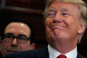 With Treasury Secretary Steve Mnuchin standing behind him, US President Donald Trump smiles while listening to remarks before signing an executive order making it easier for Americans to buy bare-bones health insurance plans and circumvent Obamacare rules at the White House in Washington, US, October 12, 2017. Credit: Reuters/Kevin Lamarque/Files