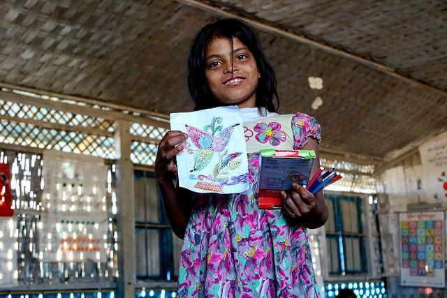 A Rohingya girl proudly holds up her drawing at a UNICEF school at Balukhali camp, Bangladesh. Credit: Farid Ahmed/IPS