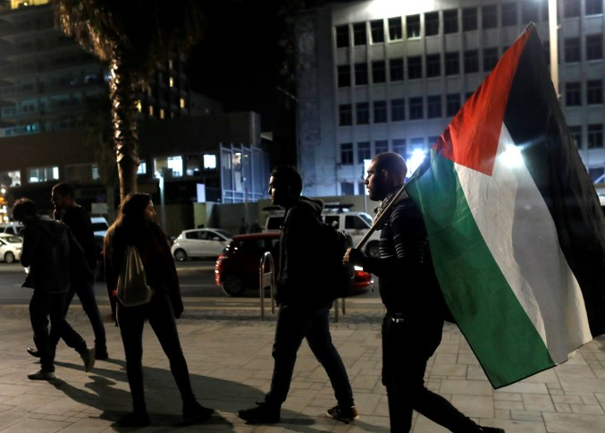 A protester carries a Palestinian flag at the end of a demonstration against US President Donald Trump's decision to recognise Jerusalem as Israel's capital opposite to the American embassy in Tel Aviv, Israel December 12, 2017. Credit: Reuters/Nir Elias