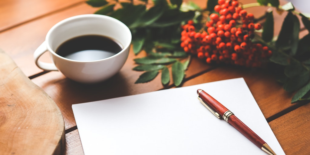 Coffee cup, paper and pen on desk — 5 Best Online Grammar Tools for Flawless Writing