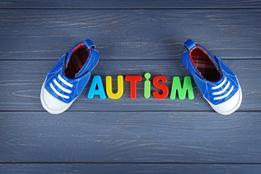 Word AUTISM with kids shoes on wooden background - Tech Innovations That Help Autistic Kids in Homeschooling