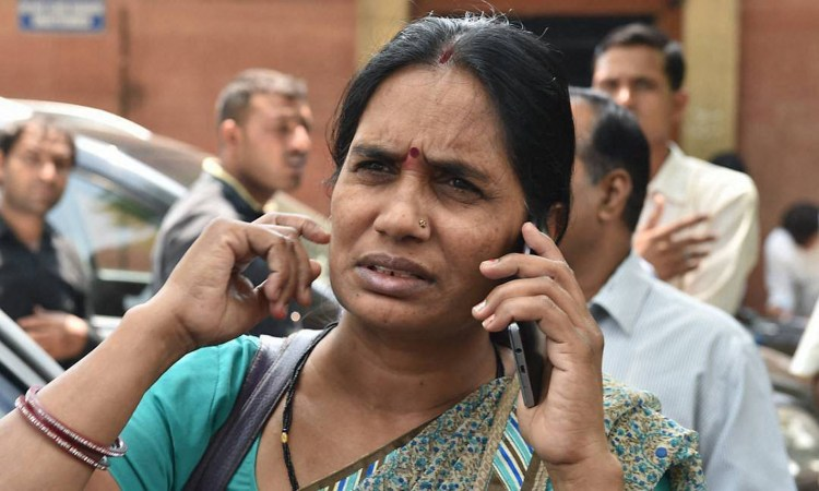 New Delhi: Nirbhaya's mother talks on phone at the Supreme Court in New Delhi on Friday. The apex court has confirmed death sentence for the four convicts of Nirbhaya gang rape case who raped and tortured the 23-year-old medical student on a moving bus in Delhi on her way home on Dec 16, 2012. PTI Photo by Manvender Vashist(PTI5_5_2017_000041B) *** Local Caption ***