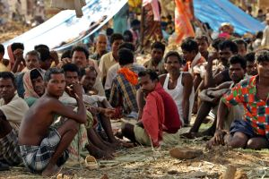 Indian tribal people sit at a relief camp in Dharbaguda, in the central state of Chhattisgarh, March 8, 2006. Violence in Chhattisgarh, one of India's poorest states, has mounted since the state government set up and started funding an anti-Maoist movement. Picture taken March 8, 2006.   REUTERS/Kamal Kishore
