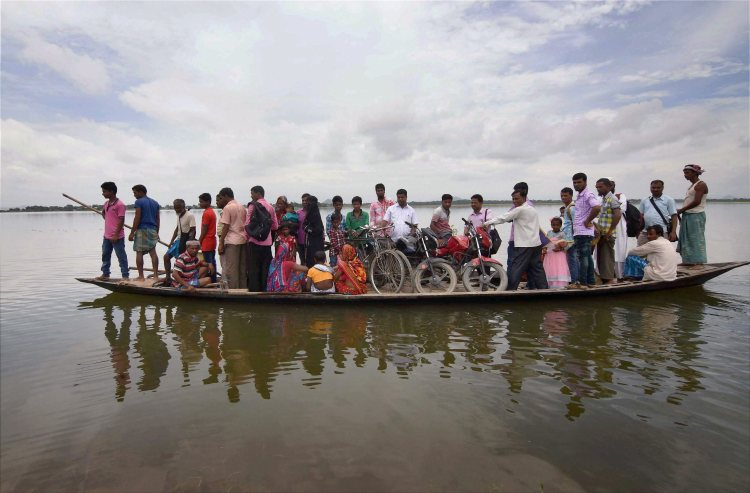 Morigaon: Villagers sit on a boat as they are transported to safety after their houses got submerged in flood waters at Balimukh village in Morigaon district of Assam. PTI Photo(PTI7_1_2017_000189B)