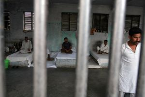 Inmates rest behind bars in a barrack at Kotbhalwal central jail in Jammu May 18, 2011. Jail authorities have formed a 20-member pipe band of a team of prisoners who are being trained to play and perform musical instruments. Once the band is ready, they will be sent to perform at weddings and other social functions, a jail superintendent said. The main aim of creating the pipe band is to develop relations of these prisoners with the rest of the outside world and to involve them in various social functions so as to change their mindset, the superintendent added.  Picture taken May 18, 2011. REUTERS/Mukesh Gupta (INDIAN-ADMINISTERED KASHMIR - Tags: CRIME LAW SOCIETY ENTERTAINMENT)