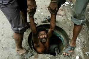 An Indian labourer is lowered to clean a sewage hole in the eastern Indian city of Kolkata December 16, 2005. Acceleration in economic growth has made India amongst the 10 fastest growing developing countries. Yet, about 30 percent of India's more than one billion people live below the official poverty line of 2,100-2,400 calories a day. REUTERS/Parth Sanyal - RTR1B4O1