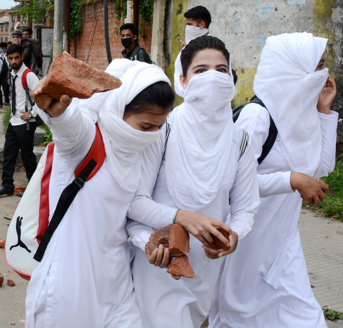 Srinagar: Girl Students holding stones to throw it on police during fresh clashes between students Police,Outside Gandhi College in Srinagar on Monday. PTI Photo(PTI5_22_2017_000174B)