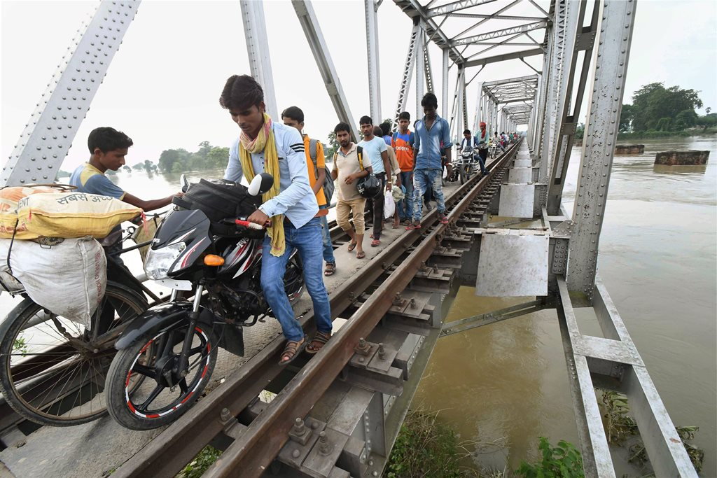 Chanpatia: Flood-affected people passing through a railway bridge at Chanpatia in West Champaran on Friday. PTI Photo(PTI8 18 2017 000116A)