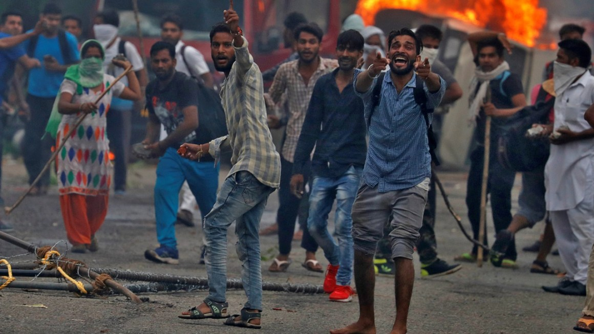 People react during violence in Panchkula, India, August 25, 2017. REUTERS/Cathal McNaughton - RTS1DAPB