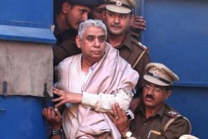 Controversial religious leader Sant Rampal stands by the door of a police van as he is brought to court surrounded by police personnel in Chandigarh, India. Police arrested the 63-year-old self-styled Hindu guru at his sprawling ashram in the northern part of the country, ending a days-long standoff in which six people died and hundreds were injured. He is wanted for questioning in a 2006 murder case but has repeatedly ignored orders to appear in court. (AP)