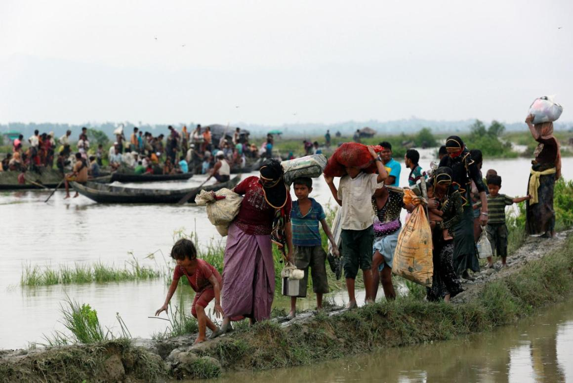 Rohingya refugees walk on a muddy path as others travel on a boat after crossing the Bangladesh-Myanmar border, in Teknaf, Bangladesh, September 6, 2017. REUTERS/Danish Siddiqui