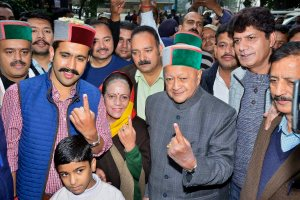 Rampur: Himachal Pradesh Chief Minister Virbhadra Singh with wife Partibha Singh and son Vikrmaditya Singh showing their inked finger after they cast their vote at a polling booth, in Rampur on Thursday. PTI Photo (PTI11_9_2017_000026B)