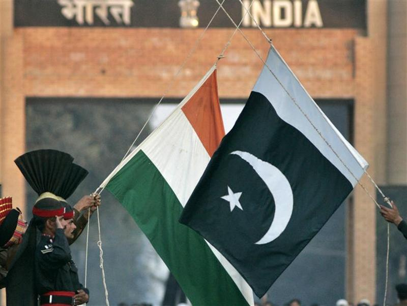 Pakistani Rangers and Indian Border Security Force personnel (obscured) lower the flags of the two countries during a daily flag lowering ceremony at the India-Pakistan joint border at Wagah, December 14, 2006. REUTERS/Mian Khursheed/Files