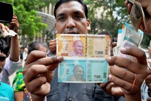 New Delhi: A man shows new currency notes of Rs 200 and Rs 50 outside the Reserve Bank of India in New Delhi on Friday.This is the first time that Rs 200 banknotes were introduced in India. PTI Photo(PTI8_25_2017_000039B)