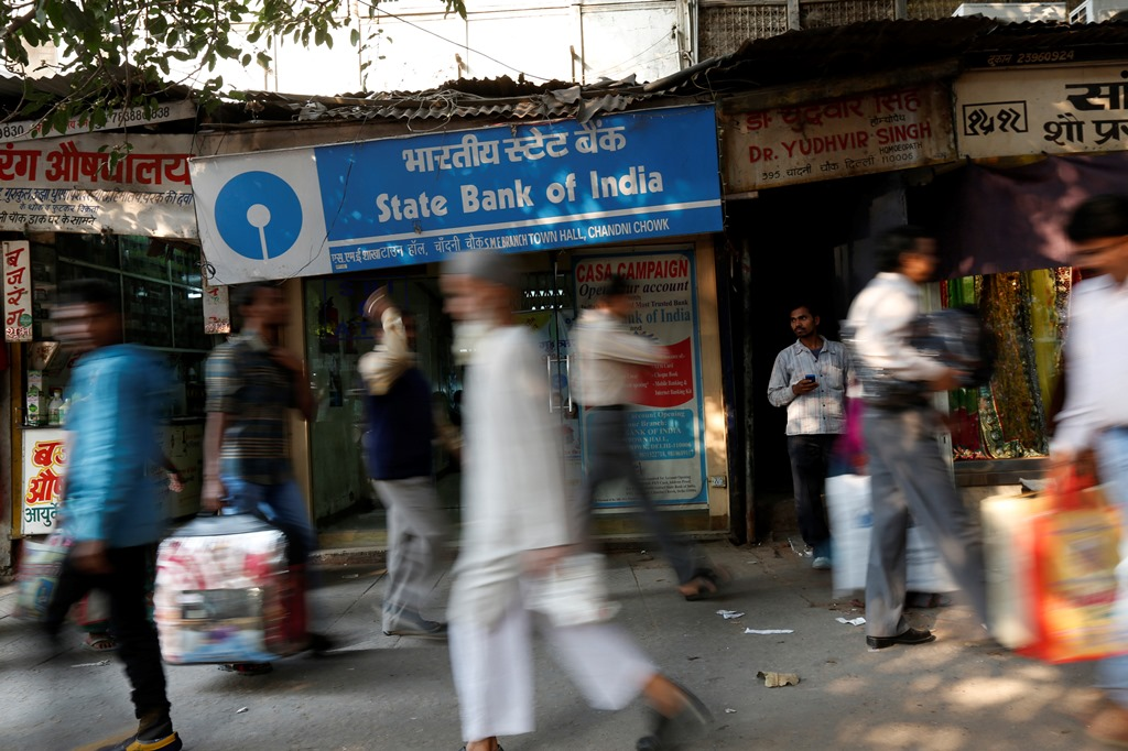 Commuters walk past a State Bank of India branch in the old quarters of Delhi November 13, 2013. State Bank of India (SBI) posted its steepest quarterly profit fall in more than two years as nonperforming loans increased, underlining the difficulties the bank's first chairwoman faces in keeping a lid on deteriorating assets. REUTERS/Mansi Thapliyal (INDIA - Tags: BUSINESS) - RTX15BLY
