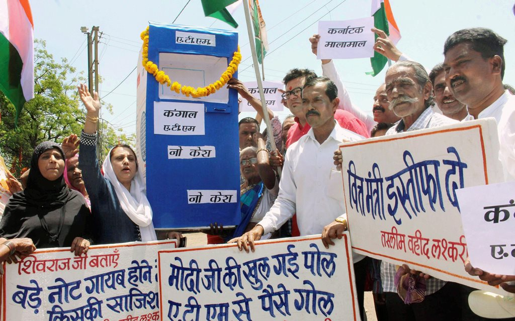 Bhopal: Congress party activists stage a protest against cash crunch as most of the ATMs are either not working or running out of cash in Bhopal on Wednesday. PTI Photo(PTI4_18_2018_000030B)