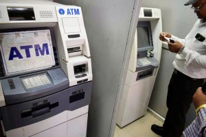 Allahabad: A man stand next to an out-of-service Automated Teller Machine (ATM) in Allahabad on Wednesday. PTI Photo (PTI4_18_2018_000120B)