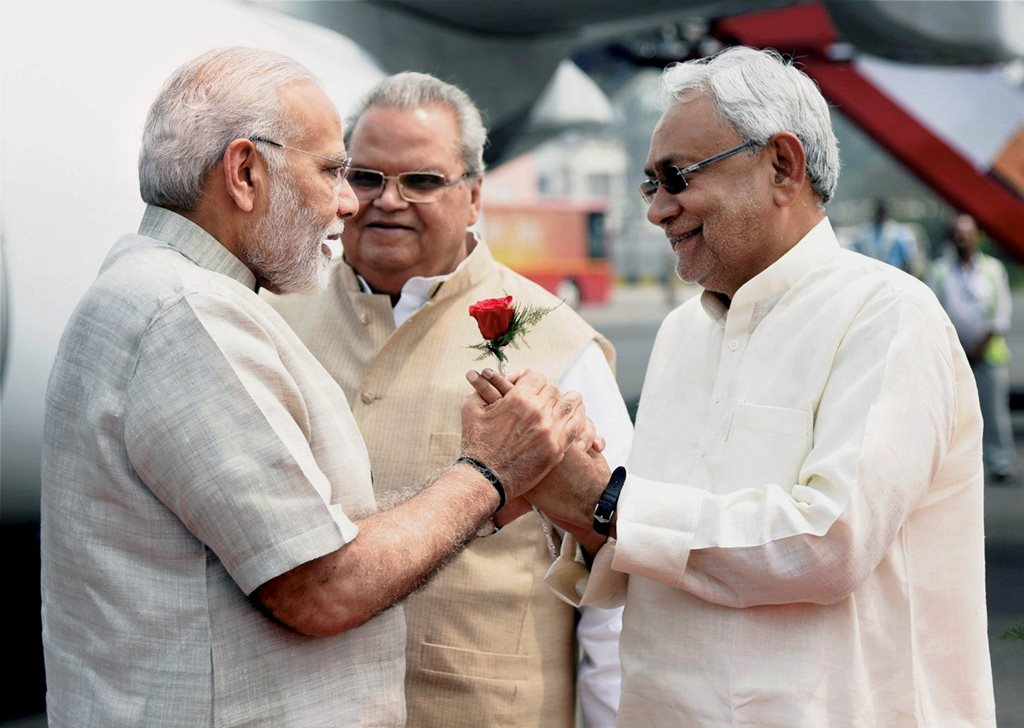 Patna: Prime Minister Narendra Modi being welcomed by Bihar Chief Minister Nitish Kumar and Bihar Governor Satyapal Malik upon his arrival at Jay Prakash Narayan International Airport in Patna on Tuesday. PTI Photo/PIB(PTI4_10_2018_000043B)