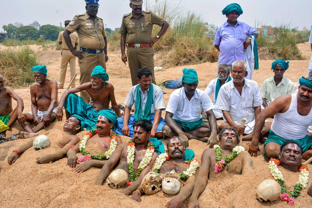 Tiruchirappalli: Farmers representing National South Indian River Link Association lie neck deep in Cauvery river bed with rose garlands to signify 'death' as part of their protest demanding the constitution of Cauvery Management Board in Tiruchirappalli on Friday. PTI Photo (PTI4_6_2018_000206B)