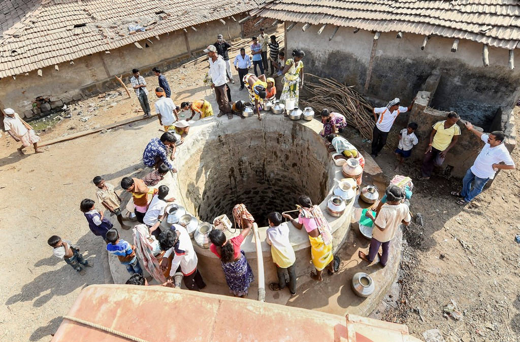 Mokhdad: People collect water from a well supplied by the government tankers at a tribal village in Mokhdad district of Maharashtra on Thursday. The region is facing acute shotrtage of water and government tankers supply water to the villagers only one time a day. PTI Photo by Shashank Parade (PTI4_19_2018_000104B)