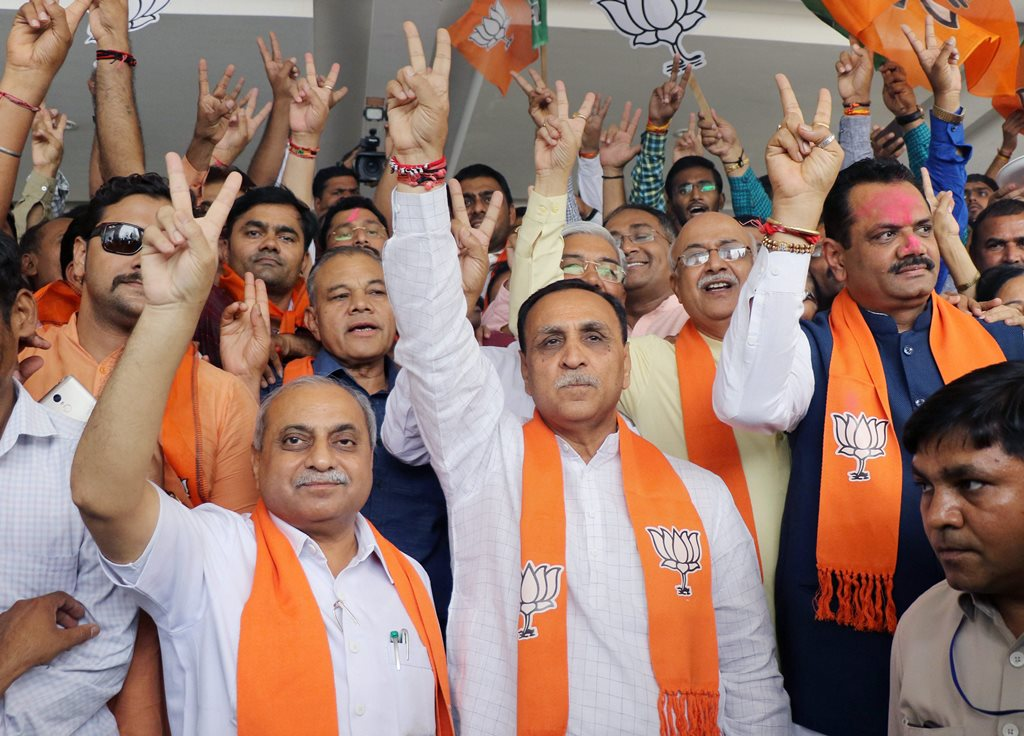 "Gandhinagar: Gujarat Chief Minister Vijay Rupani, deputy Chief Minister Nitin Patel, State President Jitu Vaghani and other BJP leaders show victor sign as they celebrate the party's performance in Karnataka Assembly elections, at the BJP office ""Kamalam"" at Gandhinagar on Tuesday. PTI Photo (PTI5_15_2018_000073B)"