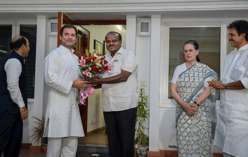 New Delhi: JD(S) leader and Karnataka chief minister-designate H D Kumaraswamy presents a bouquet to Congress President Rahul Gandhi, during a meeting at latter's residence, in New Delhi, on Monday. Former Congress president Sonia Gandhi is also seen. (PTI Photo/Manvender Vashist)(PTI5_21_2018_000188B)