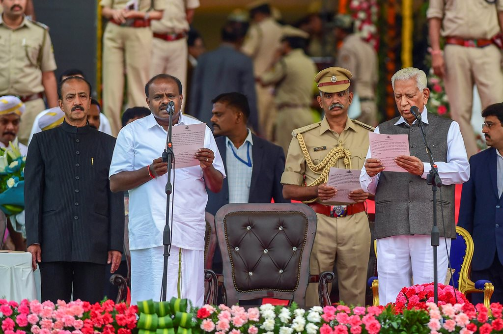 RPT with add info::: Bengaluru: Karnataka Governor Vajubhai Vala administers the oath to JD(S) leader H D Kumaraswamy as Karnataka Chief Minister during the swearing-in ceremony of JD(S)-Congress coalition government, in Bengaluru, on Wednesday. (PTI Photo/Shailendra Bhojak) (PTI5_23_2018_000130B)