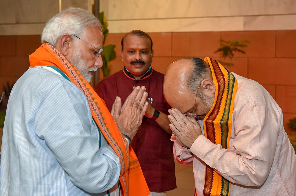 New Delhi: Prime Minister Narendra Modi is greeted by BJP President Amit Shah as he arrives for BJP Parliamentary Board meeting after Karnataka Assembly elections result 2018, in New Delhi, on Tuesday. (PTI Photo/Kamal Kishore) (PTI5_15_2018_000209B)