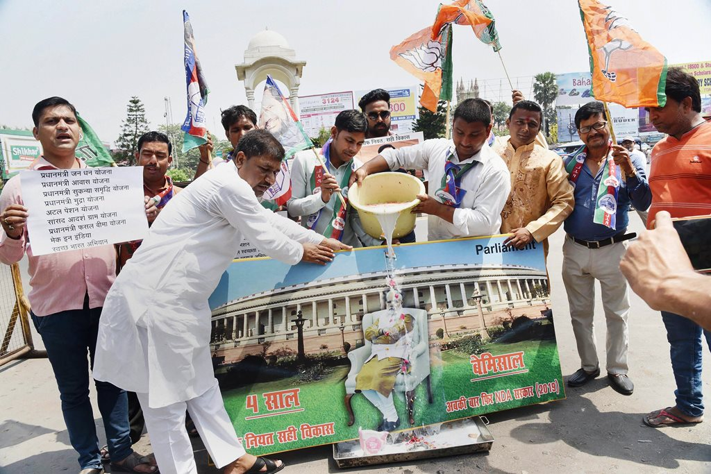 Patna: NDA supporter milk bath a photo of PM Narendra Modi as they celebrate the 4th anniversary of the Narendra Modi-led BJP government, in Patna on Saturday
