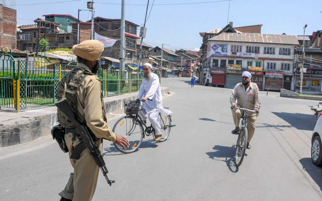 A security person stops bicycle riders on a deserted street during a curfew imposed to maintain law and order, following a strike call given by joint Hurriyat leadership, in Srinagar on Saturday, June 02, 2018. Credit: PTI