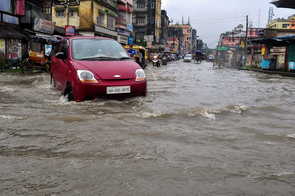 Silchar: A car wades through a flooded street after heavy downpour in Silchar, Assam on Thursday, June 14, 2018. (PTI Photo) (PTI6_14_2018_000072B)