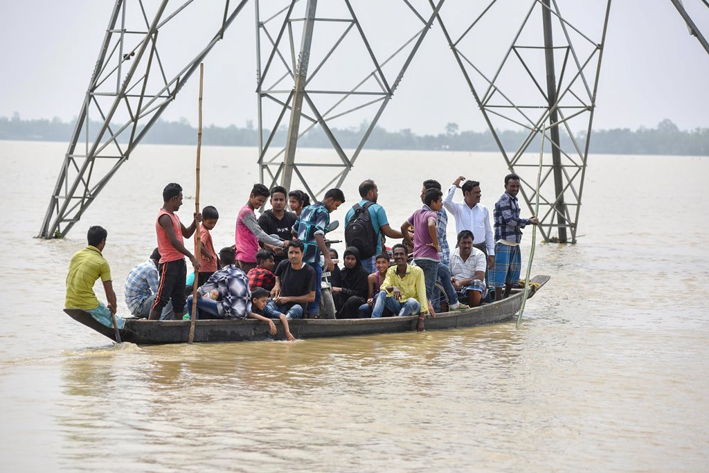 Hojai: Villagers travel in a boat to cross across flood water, in Hojai on Sunday, June 17, 2018. (PTI Photo) (PTI6_17_2018_000065B)