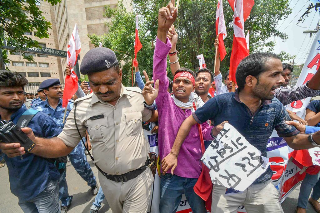 Patna: Police personnel detain All India Students Federation activists during a protest against the low pass percentage in the Intermediate exams, in Patna on Wednesday, June 13, 2018. (PTI Photo) (PTI6_13_2018_000047B)