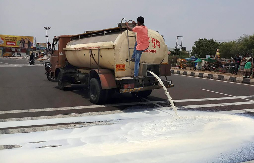 Pune: Farmers from Ahmednagar spill milk down a road during a state-wide protest, in Pune on Friday, June 01, 2018. Farmers today launched a 10-day-long agitation as part of a nationwide strike to press for their demands, including waiver of loans and the right price for crops. (PTI Photo) (PTI6_1_2018_000092B)