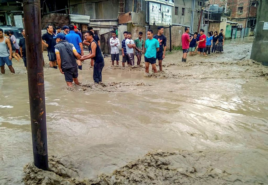 Imphal: People walk through the flood waters after heavy rains, in Imphal on Wednesday, June 13, 2018. (PTI Photo)(PTI6_13_2018_000235B)