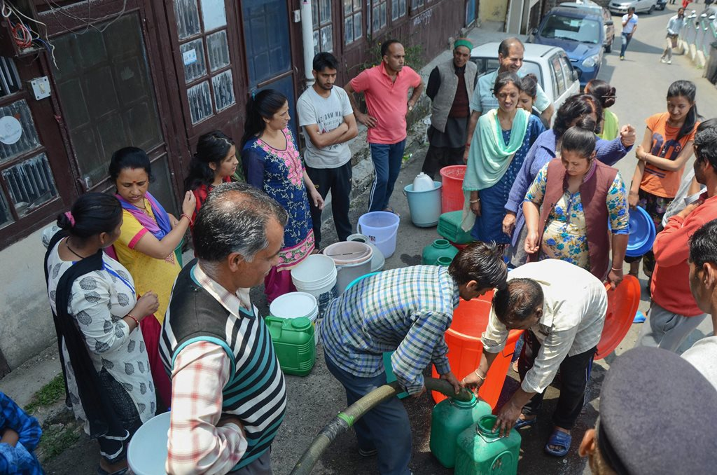 Shimla: People wait to collect water from a tanker, as the city faces acute shortage of drinking water, in Shimla on Wednesday, May 30, 2018. (PTI Photo) (PTI5_30_2018_000115B)