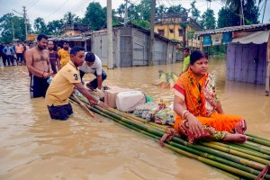 Kailashahar: A woman on a bamboo raft carrying food and water through a flooded street, in Kailashahar on Friday, June 15, 2018. (PTI Photo) (PTI6_16_2018_000101B)