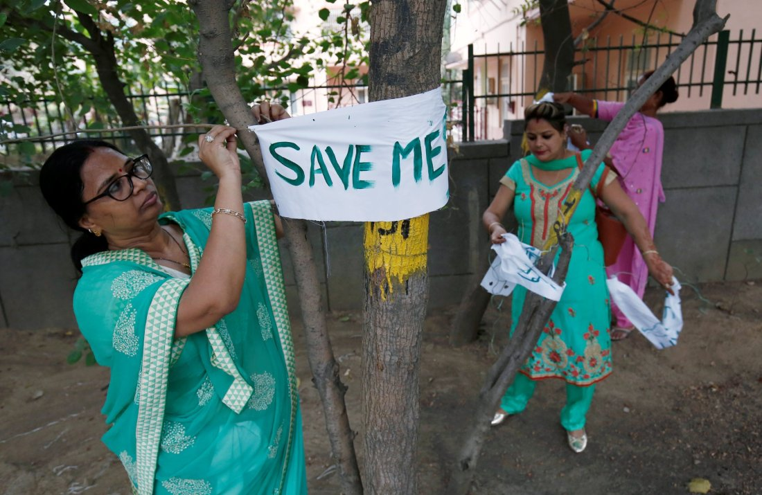"A women tie banners on trees during ""Save The Tree Campaign"" in New Delhi, India, June 26, 2018. REUTERS/Adnan Abidi"