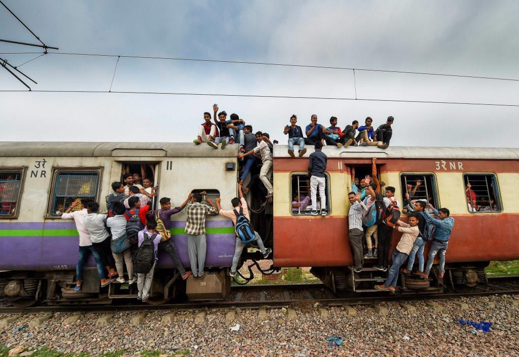 EDS PLS TAKE NOTE OF THIS PTI PICK OF THE DAY::::::::: Ghaziabad: Commuters hang on the gates and sit on the roof while traveling by a crowded train on World Population Day, at Noli Railway Station near Ghaziabad on Wednesday, July 11, 2018. The theme of World Population Day 2018 is ''Family planning is a human right'. (PTI Photo/Manvender Vashist) (PTI7_11_2018_000053A)(PTI7_11_2018_000186B)