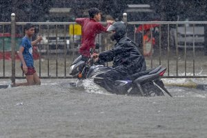 Mumbai: A motorcyclist moves through a waterlooged road during heavy rains, at King Circle in Mumbai on Tuesday, July 10, 2018. (PTI Photo/Shashank Parade) (PTI7_10_2018_000103B)