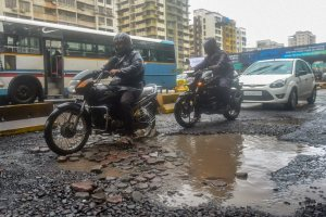 Mumbai: Commuters ride past pot-holes filled road after heavy rainfall, in Mumbai on Monday, July 9, 2018. (PTI Photo/Mitesh Bhuvad) (PTI7_9_2018_000181B)