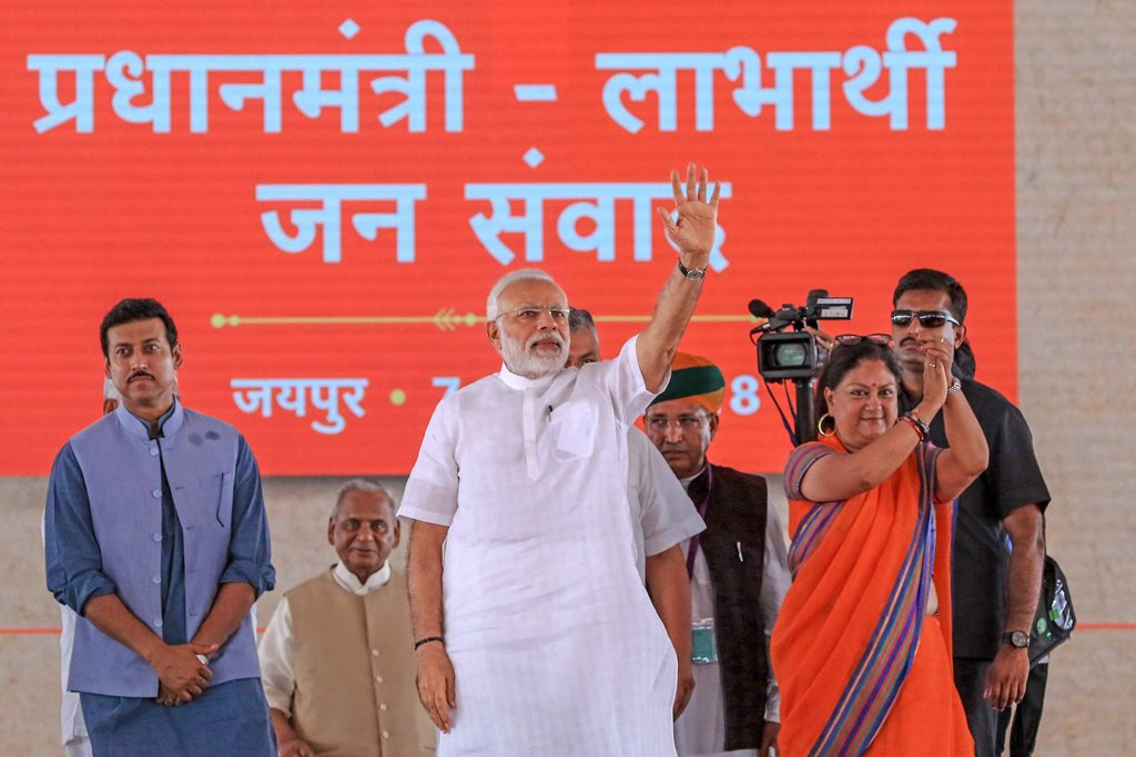 Jaipur: Prime Minister Narendra Modi waves to the beneficiaries of various welfare schemes of the BJP government, at a meeting in Jaipur on Saturday, July 7, 2018. Rajasthan Chief Minister Vasundhara Raje and Union minister Rajyavardhan Singh Rathore are also seen. (PTI Photo) (PTI7_7_2018_000092B)