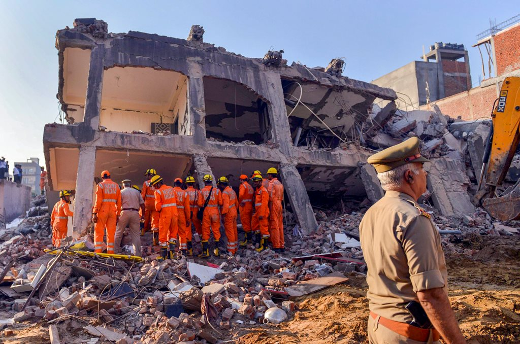 Greater Noida: Rescue workers search for survivors under the debris of a collapsed building at Shahberi village, in Greater Noida West on Wednesday, July 18, 2018. A six-storey under-construction building collapsed in Greater Noida, killing at least two persons and trapping several others under the debris. (PTI Photo) (Story no DES49)(PTI7_18_2018_000014B)