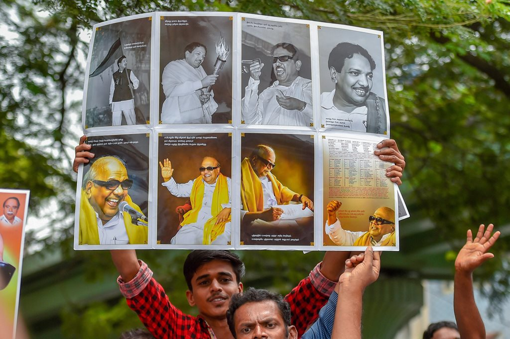 Chennai: A DMK supporter displays a poster as he stands with others near the Kauvery Hospital, where the party President M Karunanidhi is undergoing treatment, in Chennai on Tuesday, Aug 7, 2018. Supporters have started thronging the hospital after Karunanidhi's conditions, reportedly, deteriorated on Monday. (PTI Photo) (PTI8_7_2018_000152B)