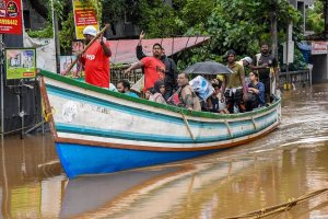 Kochi: Rescue workers row a boat carrying locals who were stranded in floods following heavy monsoon rainfall, in Kochi on Saturday, Aug 18, 2018. (PTI Photo) (PTI8_18_2018_000082B)