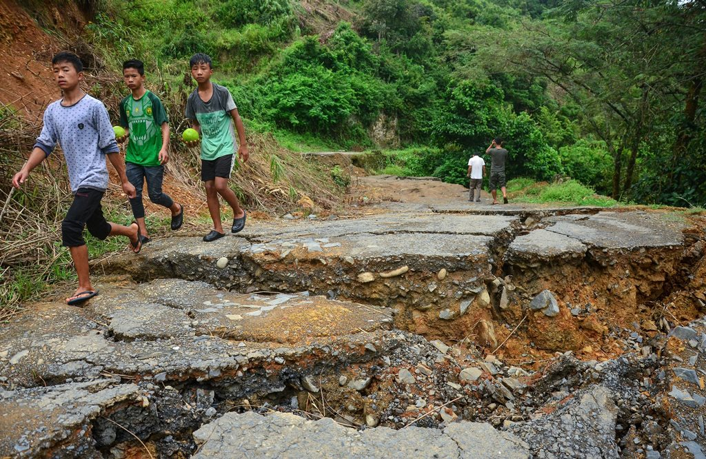 Phek: Children walk past the landslide area on the National Highway 202 at Meluri under Phek district in Nagaland on Wednesday, August 29, 2018. (PTI Photo) (PTI8_29_2018_000314B)