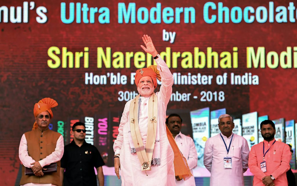 Anand: Prime Minister Narendra Modi at the inauguration of Amul's ultra-modern Chocolate Plant, in Anand, Gujarat, September 30, 2018. Gujarat Chief Minister Vijay Rupani (L) is also seen. (PIB Photo via PTI) (PTI9_30_2018_000071B)